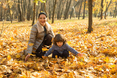 Happy mom and her toddler son in autumn park Royalty Free Stock Photos