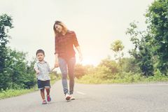 Happy mom holding hand with his son walking on the street. Happy mom holding hand with his son walking on the street background royalty free stock images