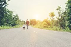 Happy mom holding hand with his son walking on the street. Happy mom holding hand with his son walking on the street background royalty free stock photos