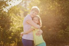 Happy mom hugs daughter teen in backlight outdoors stock photos