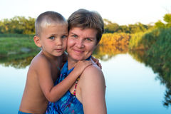 Happy mom hugs his young son. Against the backdrop of a forest lake, a wonderful summer evening. Happy mothers day in nature Royalty Free Stock Images