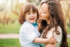 Happy mom hugs and kiss toddler kid son outdoor in spring or summer. Loving family and mothers day concept royalty free stock image