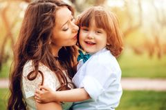 Happy mom hugs and kiss toddler kid son outdoor in spring or summer. Loving family and mothers day concept stock image