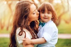 Happy mom hugs and kiss toddler kid son outdoor in spring or summer. Loving family and mothers day. Concept stock images