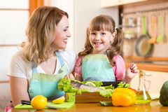 Happy mom and kid cooking healthy food in kitchen. Happy mom and kid cooking healthy food fish in kitchen at home Stock Photography