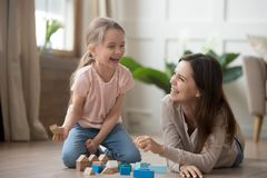 Happy mom and kid daughter laughing playing with wooden blocks royalty free stock photo