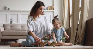 Happy mom with kid daughter playing dinosaurs sit on floor