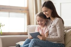 Happy mom and kid daughter using digital tablet on sofa royalty free stock image
