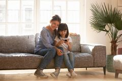 Happy mom and kid daughter using smartphone sitting on couch. Happy mom and little kid daughter enjoy using mobile apps on smartphone sitting on couch, smiling stock photo