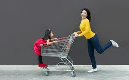 Happy mom and kid go shopping cart together. Funny action of mother and child go to modern trade or shopping center with cart, indoors, supermarket, department stock image