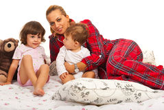 Happy mom with kids in bed Stock Images
