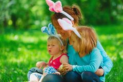 Happy mom and kids on easter eggs hunt in spring. Nature stock photography