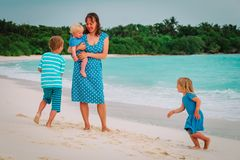 Happy mom with kids play run on tropical beach. Vacation royalty free stock photo