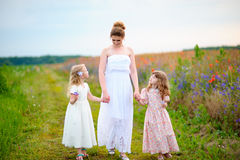 Happy mom with kids walking near the spring field Royalty Free Stock Image