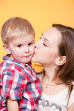 Happy mom kissing little son. Closeup portrait Stock Photography