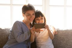 Happy mom and little child enjoy using smartphone at home. Happy mom and little child girl enjoy using smartphone apps watch cartoon make video call, smiling royalty free stock photo