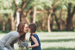 Happy mom and little daughter sitting on the lawn in the Park. stock photos