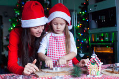 Happy mom and little girl in Santa hat baking Royalty Free Stock Images