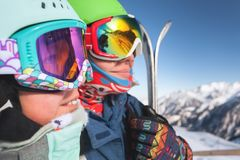 Happy mom and little girl sitting on the chair on ski lift smiling and wearing ski masks with mountain on background royalty free stock image