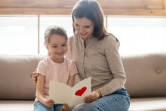 Happy mom and little kid daughter holding reading greeting card. Happy family young mom and little cute kid daughter holding reading greeting card with red heart stock photo