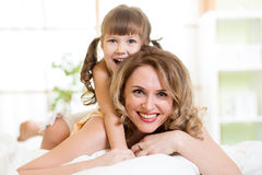 Happy mom playing with her kid in bed enjoying Stock Photography