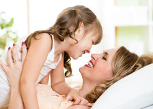 Happy mom playing with her kid in bed enjoying. Happy middle-aged mom playing with her kid daughter in bed enjoying  sunny morning in home bedroom Stock Image