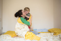 Happy mom playing with her son in bed  a relaxed morning Royalty Free Stock Photo