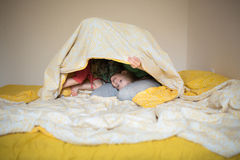 Happy mom playing with her son in bed  a relaxed morning Royalty Free Stock Image