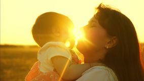 Happy mom plays with child, mother throws child into air in bright rays of the sun. slow shooting close-up