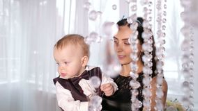 Happy mom plays with her little son in a bright room with beautiful chandelier. Happy mom plays with her little son in a bright room, they look at the beautiful stock video