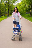 Happy mom pushing pram with toddler in park Stock Photography