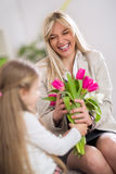 Happy mom receiving flowers from her daughter Royalty Free Stock Photography