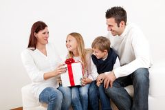 Happy mom receiving a gift from her kids. At home Stock Image