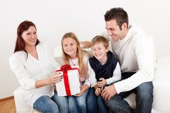 Happy mom receiving a gift from her kids. At home Royalty Free Stock Photos