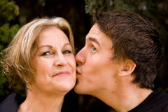 Happy mom smiling and son giving kiss. Mom smiling with son giving kiss royalty free stock photography