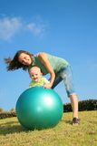 Happy mom and son. Young blond happy mom is engaged with his little blond child on a gymnastic ball on the green grass and the blue sky Royalty Free Stock Images