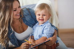 Happy mom with son drawing on the floor. At home Royalty Free Stock Photo