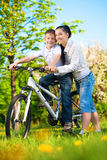 Happy mom and son in a green park with a bike. Mom and son in a green park with a bike Stock Images