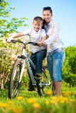 Happy mom and son in a green park with a bike. Mom and son in a green park with a bike Royalty Free Stock Image