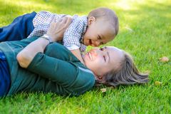 Happy mom and son are lying on the grass in the park royalty free stock photos