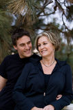 Happy mom and son by pine tree. Happy mom and son smiling by pine tree Royalty Free Stock Photography