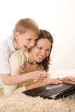 Happy mom and son playing with laptop. On the floor Stock Image