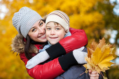 Happy Mom and son are playing in a yellow autumn. Mom and son on a autumn park background Stock Photos