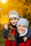 Happy Mom and son are playing in a yellow autumn Stock Images
