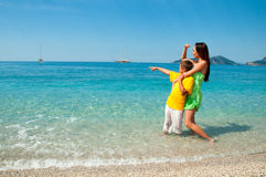 Happy mom and son on sea beach looking Royalty Free Stock Images