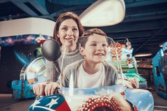 Happy mom and son on toy motorcycle royalty free stock photos