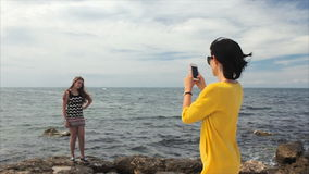 Happy mom taking photo your daughter with smartphone on the see background stock footage