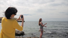 Happy mom taking photo your daughter with smartphone on the see background stock video