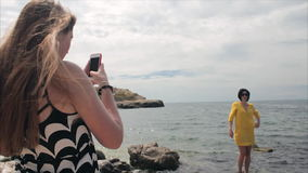 Happy mom taking photo your daughter with smartphone on the see background stock video footage