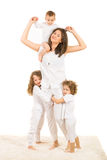 Happy mom with three kids. Happy mother with her kids playing home and standing on carpet against white background Stock Images